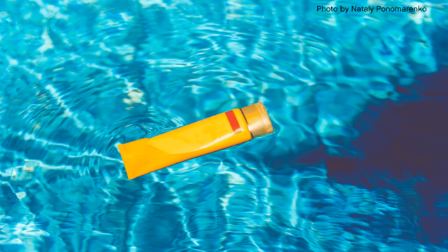 Sunscreen bottle floating in pool